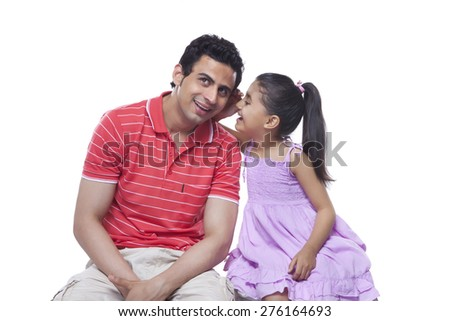 Happy daughter whispering in father's ear over white background - stock photo