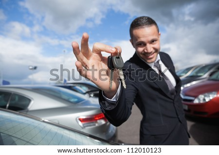 Happy dealer holding car keys outdoors - stock photo