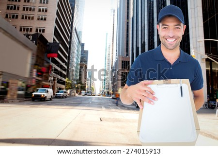Happy delivery man with package and clipboard against new york street - stock photo