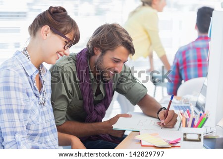 Happy designers working on a document with colleagues working behind - stock photo