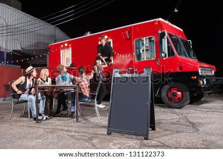 Happy diners at food truck with blank sign - stock photo