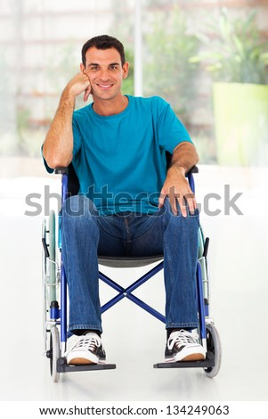 happy disabled man sitting on wheelchair at home - stock photo