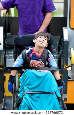 Happy disabled seven year old boy being transported on handicap school bus lift - stock photo