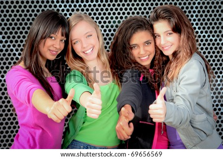 Happy diverse group of teenage girls showing thumbs up - stock photo