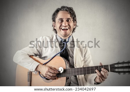 Happy doctor playing the guitar  - stock photo