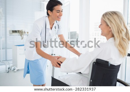 Happy doctor smiling at her patient in wheelchair in hospital - stock photo