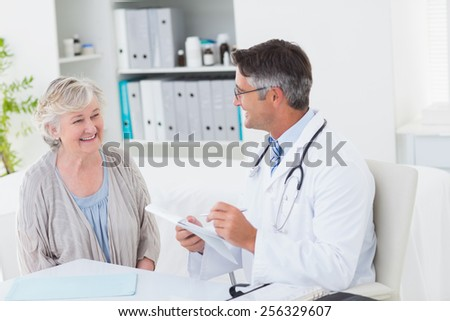 Happy doctor writing prescriptions for senior female patient in clinic - stock photo