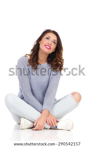 Happy Dreamer Girl Looking Up. Smiling young woman in sweater and jeans sitting on a floor with legs crossed looking up. Full length studio shot isolated on white. - stock photo