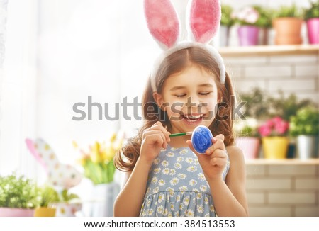 Happy easter! A beautiful child girl painting Easter eggs. Happy family preparing for Easter. Cute little child girl wearing bunny ears on Easter day. - stock photo
