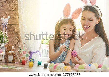 Happy easter! A mother and her daughter painting Easter eggs. Happy family preparing for Easter. Cute little child girl wearing bunny ears on Easter day. - stock photo
