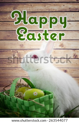 happy easter against easter bunny rabbit sitting with basket of easter eggs - stock photo