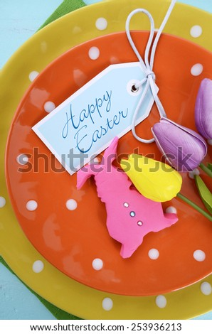 Happy Easter bright color orange, yellow and green polka dot theme table place setting with pink fondant bunny cookie and tulips on pale aqua blue distressed wood table, vertical with greeting tag. - stock photo
