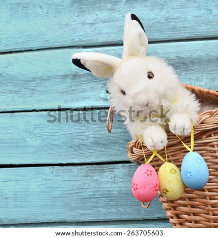 Happy Easter Bunny in a basket and eggs on a blue wooden background. - stock photo