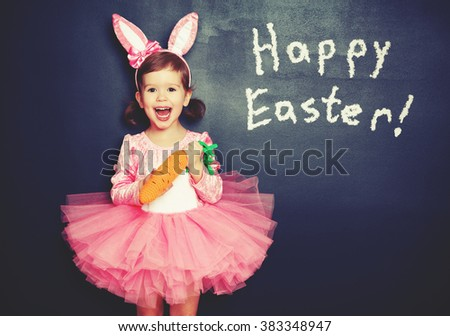 Happy Easter! child girl in costume bunny rabbit with e carrot about blackboard - stock photo