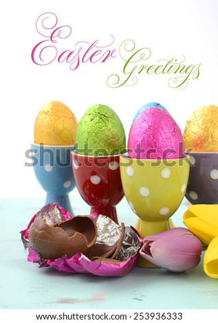 Happy Easter chocolate eggs wrapped in bright color foil in red, yellow, blue, green and purple polka dot egg cups, vertical with sample text. - stock photo
