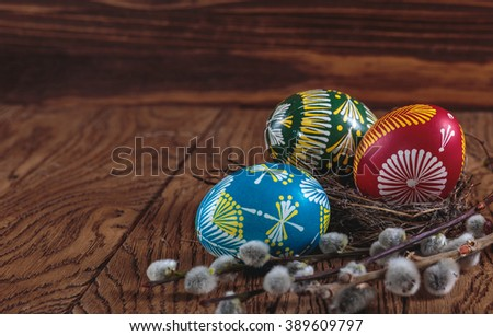 Happy Easter. colored Easter eggs and a branch blooming willow on the wooden background. Easter decoration - stock photo
