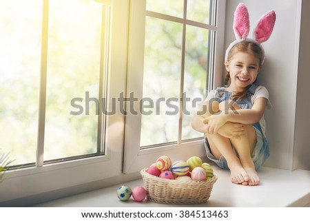 Happy Easter! Cute little child girl wearing bunny ears on Easter day. Girl sitting on the window with a basket of Easter eggs. Child girl laughs and enjoys spring and a holiday. - stock photo