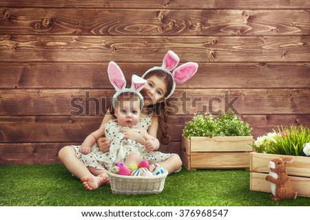 Happy Easter! Cute little children girls wearing bunny ears on Easter day. Sisters hunting for Easter eggs on the lawn near the house. Girls having fun, playing and hugging. - stock photo