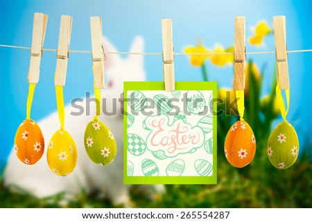 happy easter graphic against white fluffy bunny sitting beside daffodils with easter eggs - stock photo