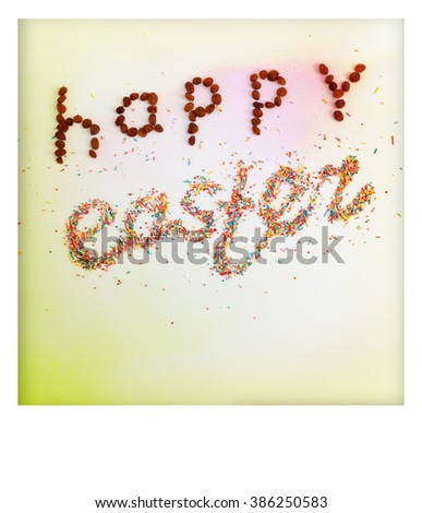 Happy Easter phrase made from raisins and colorful baking sugar over colorful background with copy space and white frame, top view - stock photo