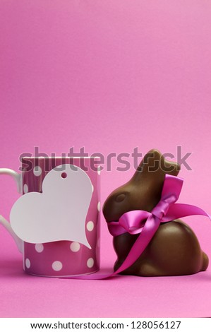 Happy Easter pink polka dot coffee or tea mug with white heart shape gift tag sign and chocolate bunny with pink ribbon. Vertical, with copy space for your text here. - stock photo