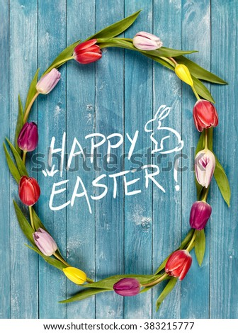 Happy Easter spring frame or oval wreath of fresh colorful tulips on blue wooden boards with a central greeting and cute bunny rabbit for a pretty card design - stock photo