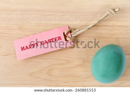 Happy Easter text on paper tag with an easter egg on wood background. - stock photo