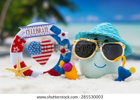 Happy egg with word celebrate  on ocean beach during patriotic holiday â?? 4th of july  - stock photo