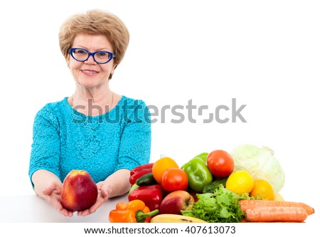 Happy elder Caucasian woman stretching hands with big red apple, vegetables and fruits are on table, isolated on white background - stock photo