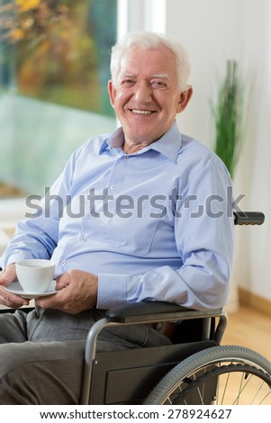 Happy elder man on wheelchair drinking coffee - stock photo