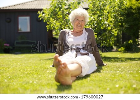 Happy elder woman sitting relaxed on grass in backyard garden and looking at camera smiling - Outdoors - stock photo