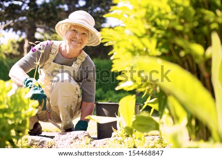 Happy elder woman with gardening tool working in her backyard garden - stock photo