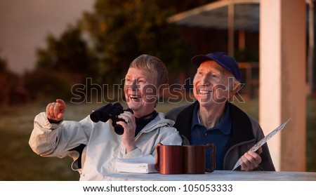Happy elderly bird watchers outside in jackets - stock photo