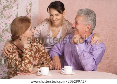Happy elderly couple and her daughter sitting at the table - stock photo