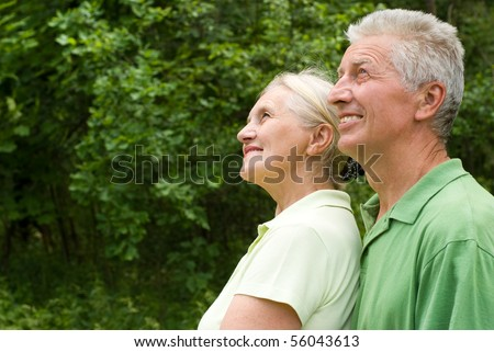 happy elderly couple in a summer park - stock photo