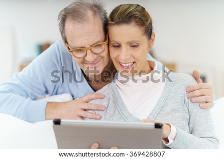 happy elderly couple looking at a tablet as they are surfing the internet - stock photo