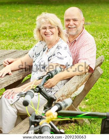 Happy elderly couple relaxing in the park after ride bike. - stock photo