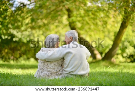 Happy elderly couple sitting in autumn park - stock photo