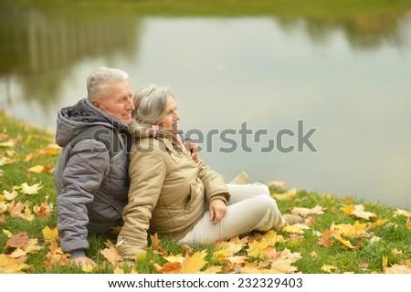 Happy elderly couple sitting near lake embracing - stock photo