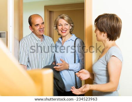 Happy elderly family couple visiting daughter at home - stock photo