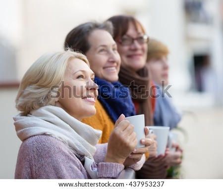 Happy elderly female friends drinking coffee at patio. Focus on blonde - stock photo