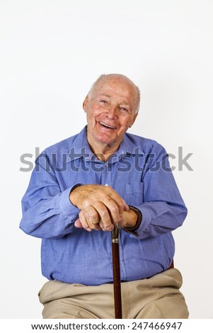 happy elderly man sitting in a chair with his walking stick - stock photo