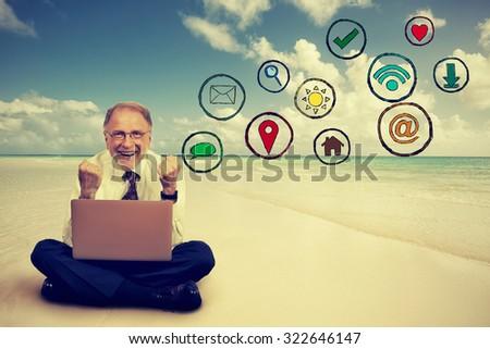 Happy elderly man working on computer using social media application on sandy tropical beach  - stock photo