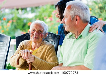 Happy elderly patient with doctor and visitor. - stock photo