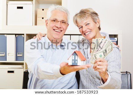 Happy elderly senior couple with small house and fan of dollar bills - stock photo
