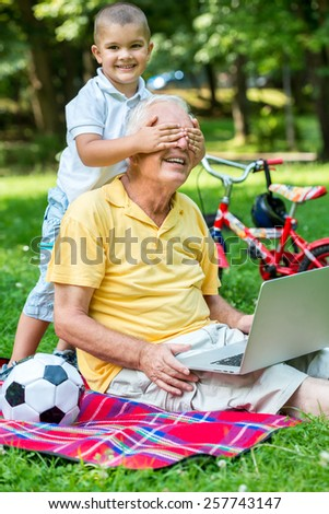 happy elderly senior grandfather and child in park using laptop computer - stock photo