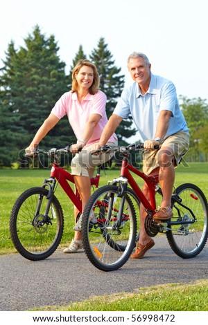 Happy elderly seniors couple biking in park - stock photo