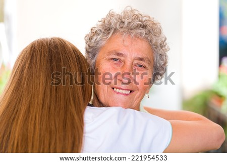 Happy elderly woman embracing with her daughter - stock photo