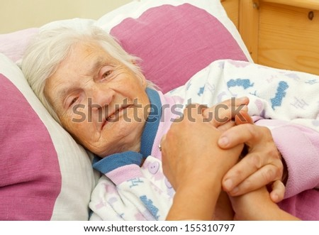 Happy elderly woman holding daughters hand in the bed - stock photo