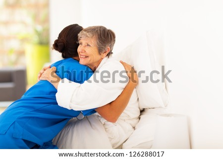 happy elderly woman hugging caregiver on bed - stock photo